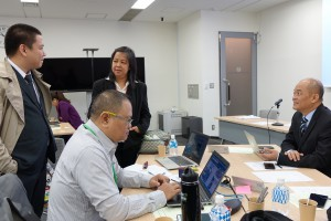 Louie A. Belleza (L) of the Embassy of the Republic of the Philippines in Japan speaking with Filipino mission members while attending day 5 sessions as an observer.
