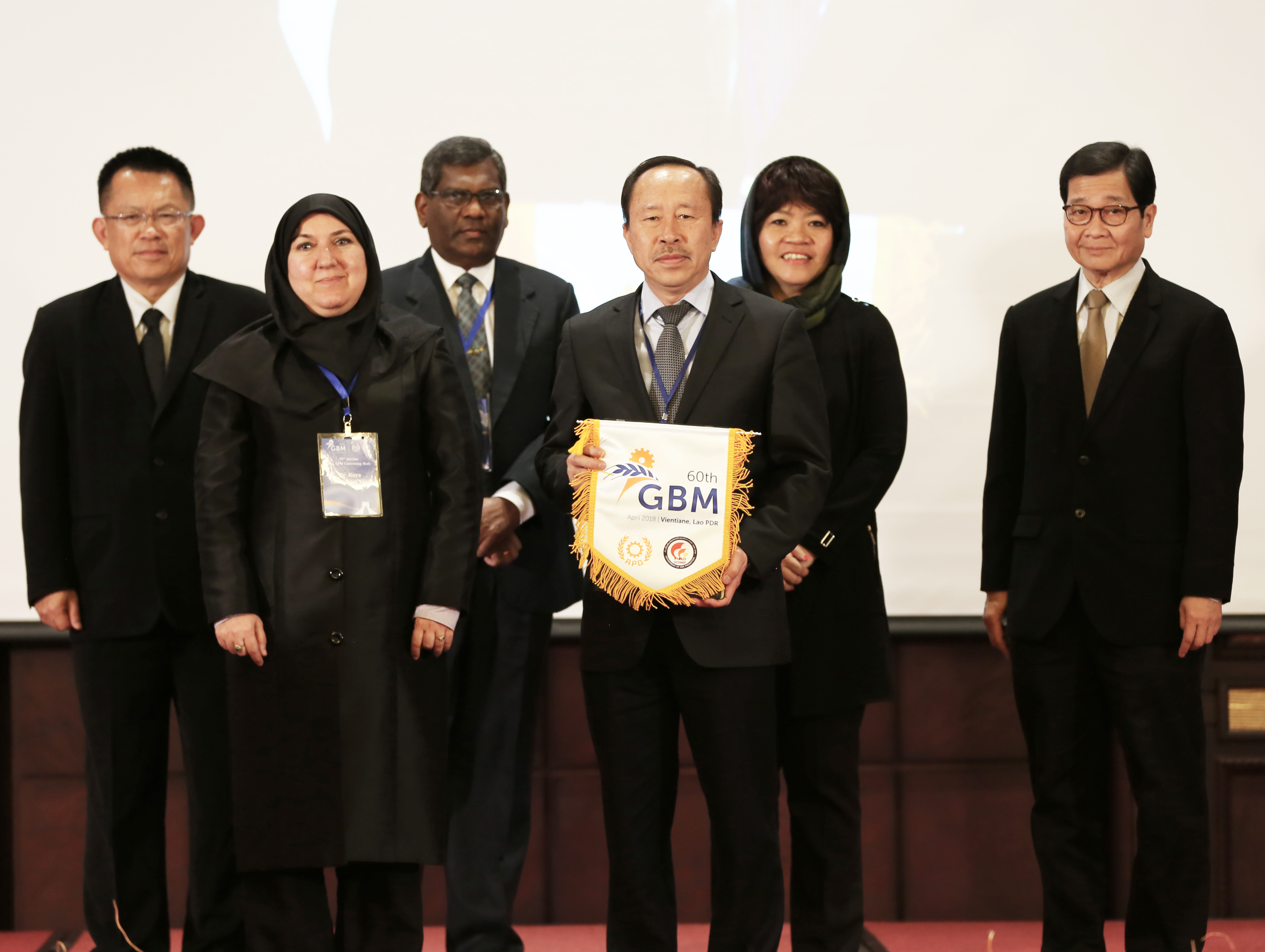 APO Director for IR Iran Dr. Roya Tabatabaei Yazdi (first row L) handing over the GBM flag to 2018 host Lao PDR, represented by APO Director Somdy Inmyxai (R). Looking on were (second row L–R): APO Director for Thailand and Second Vice Chair Dr. Somchai Harnhirun; APO Director for Sri Lanka and First Vice Chair Javigodage Jayadewa Rathnasiri; APO Director for Singapore and Chair Chew Mok Lee; and APO Secretary-General Dr. Santhi Kanoktanaporn.